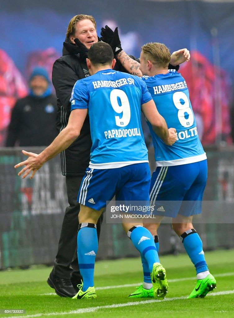 Hamburg's head coach Markus Gisdol celebrates with Hamburg's Greek defender Kyriakos Papadopoulos (9) and Hamburg's midfielder Lewis Harry Holtby (8) after Hamburg's second goal during the Bundesliga match RB Leipzig vs Hamburger SV in Leipzig on February 11, 2017. / AFP / John