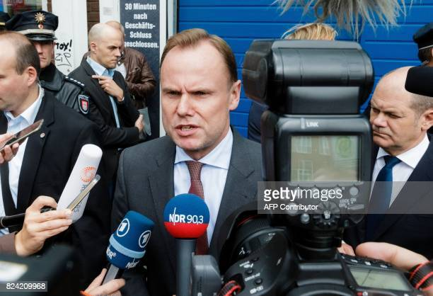 Hamburg's Interior Minister Andy Grote talks with journalists on July 29 2017 in front of a supermarket in Hamburg northern Germany one day after a...