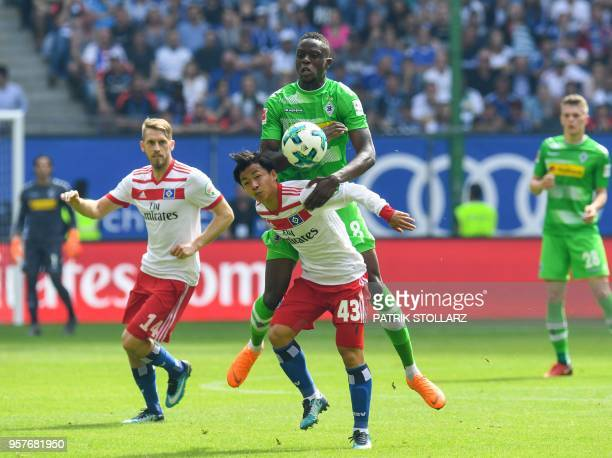Hamburg's Japanese midfielder Tatsuya Ito and Moenchengladbach's French defender Mamadou Doucoure vie for the ball during the German first division...