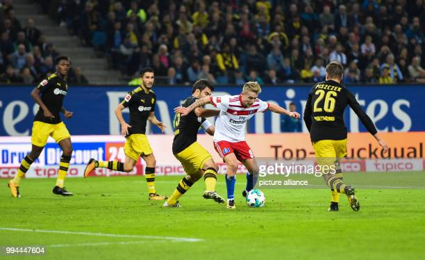 Hamburg's Lewis Holtby and Dortmund's Sokratis Papastathopoulos vie for the ball during the German Bundesliga soccer match between Hamburger SV and...