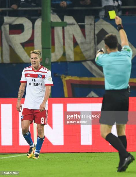 Hamburg's Lewis Holtby is shown the yellow card during the German Bundesliga soccer match between Hamburger SV and Borussia Dortmund in the...