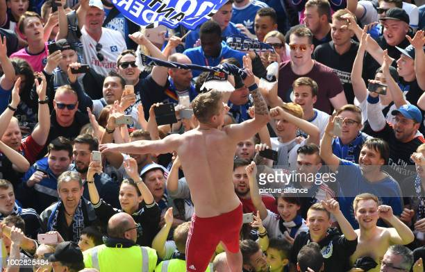 Hamburg's Lewis Holtby stands on top of the roof of the team bench and celebrates with the fans which have ran on the pitch after the German...