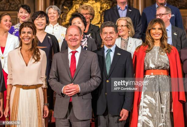 Hamburg's mayor Olaf Scholz shares a smile with husband of the German Chancellor Joachim Sauer US First Lady Melania Trump the wife of Argentina's...
