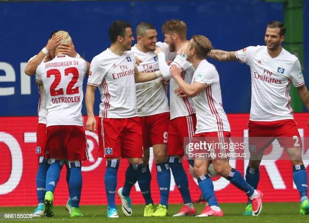 Hamburg's midfielder Aaron Hunt celebrates scoring with his team-mates during the German first division Bundesliga football match Hamburg SV v TSG...