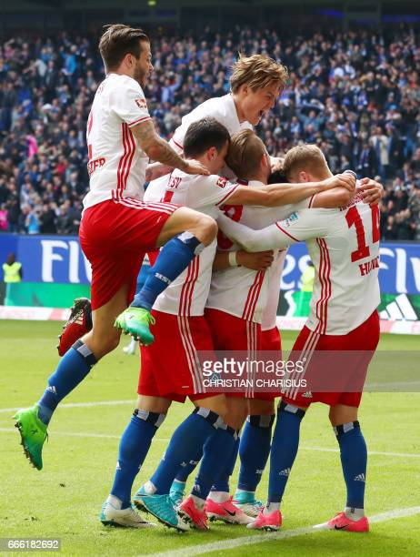 Hamburg's midfielder Aaron Hunt celebrates scoring with his teammates during the German first division Bundesliga football match Hamburg SV v TSG...