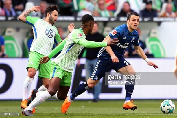 Hamburg's Serbian midfielder Filip Kostic vies for the ball with Wolfsburg's Swiss midfielder Renato Steffen and Wolfsburg's Dutch midfielder...