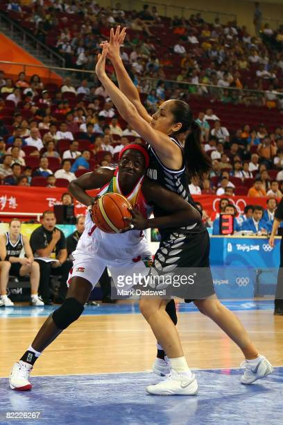 Hamchetou Maiga of Mali drives to the basket against Charmain Purcell of New Zealand during the women's preliminary basketball game at the Beijing...