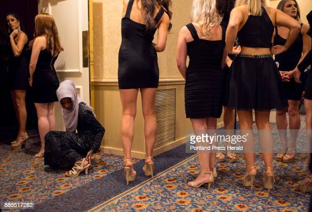 Hamdia Ahmed adjusts the strap on her high heel while standing in a line of contestants moments before walking out on to the stage at the Miss Maine...