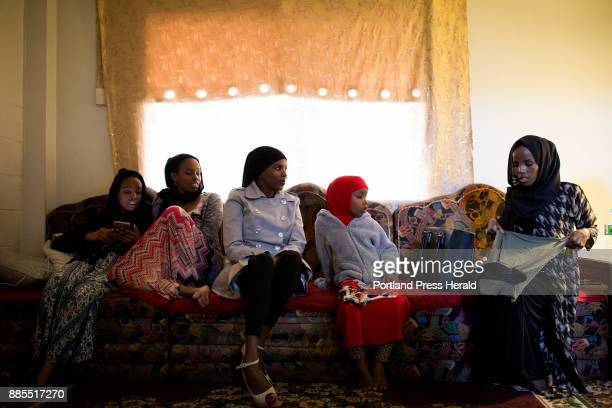 Hamdia Ahmed far right packs her suitcase at her home as she talks with from left her nieces Muno and Naimo her older sister Arianna and her niece...