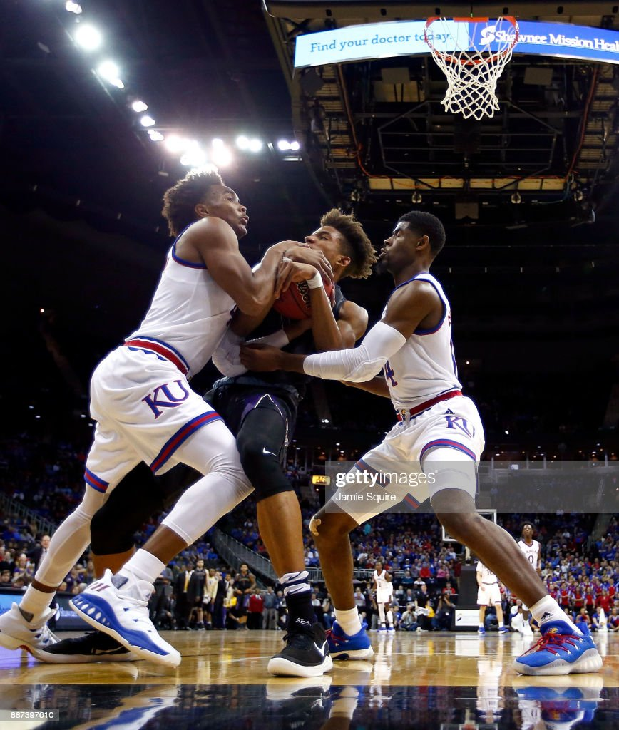 Hameir Wright #13 of the Washington Huskies wrestles with Devonte' Graham #4 and Malik Newman #14 of the Kansas Jayhawks for a loose ball during the game at the Sprint Center on December 6, 2017 in Kansas City, Missouri.