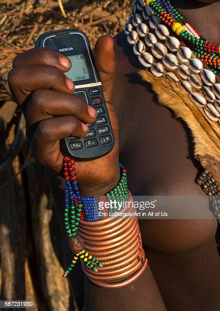 Hamer tribe girl with brass bracelets holding a nokia mobile phone omo valley turmi Ethiopia on March 13 2016 in Turmi Ethiopia