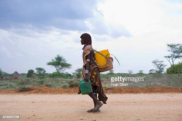 hamer woman carrying water containers on road - hugh sitton 個照片及圖片檔