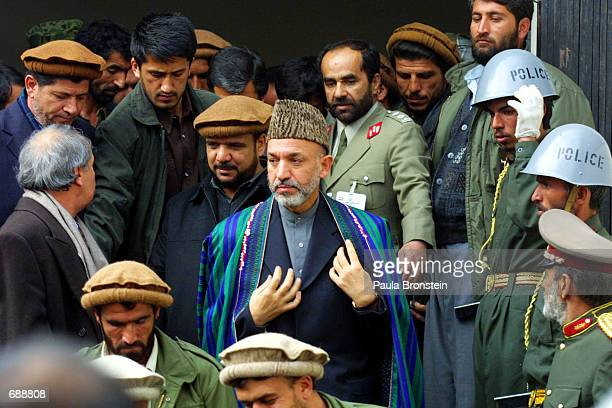 Hamid Karzai the new Prime Minister of Afghanistans interim government leaves the Interior Ministry after being sworn in December 22 2001 in Kabul...