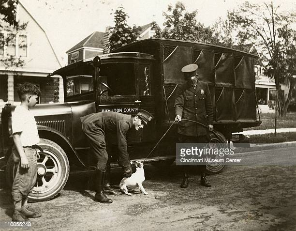 Hamilton Coounty animal control officers pose with a dog beside their truck Cincinnati Ohio 1928