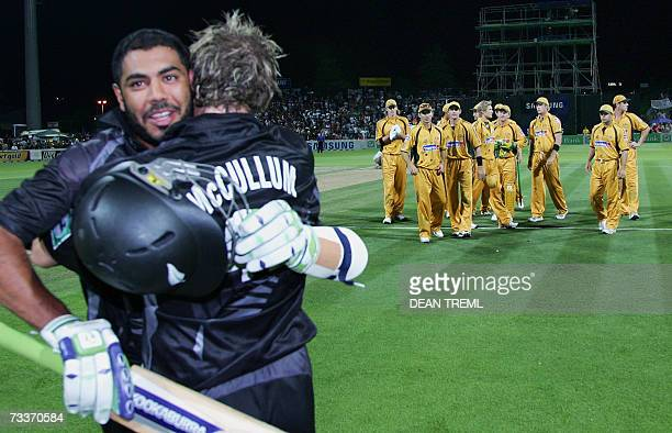 The Australian team stand dejected as New Zealand batsmen Brendon McCullum and Jeetan Patel embrance after hitting the winning runs to take match...