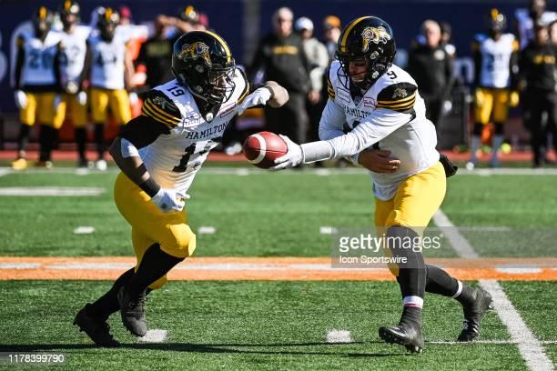 Hamilton Tiger-Cats quarterback Dane Evans hands the ball off to Hamilton Tiger-Cats running back Tyrell Sutton during the Hamilton Tiger Cats versus...