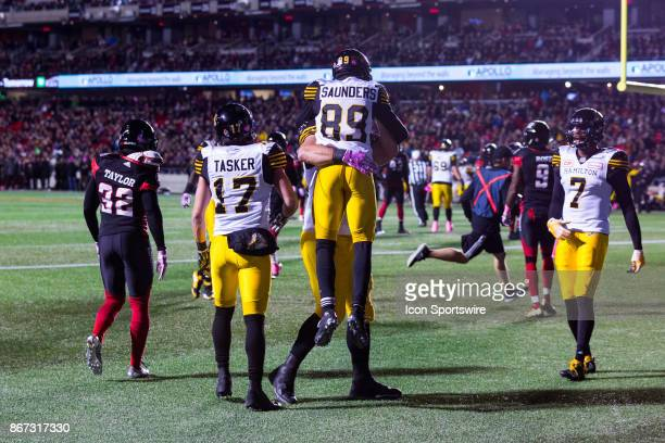 Hamilton TigerCats wide receiver Jalen Saunders leaps into the arms of a teammate to celebrate his touchdown during Canadian Football League action...