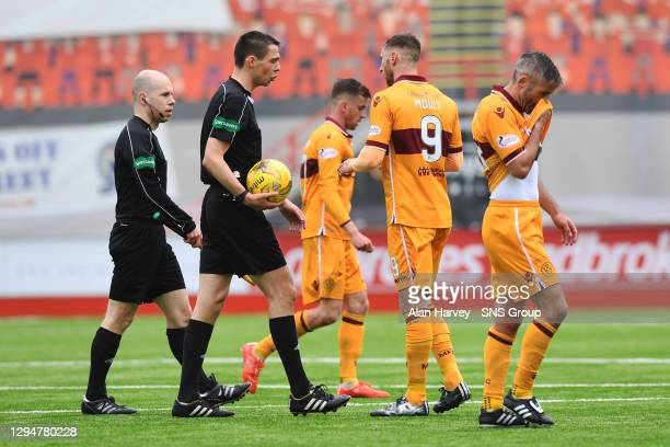 Motherwell players speak with referee Kevin Clancy as they walk off for half time.