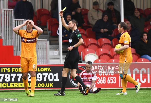 Motherwell's Carl McHugh is booked by referee Kevin Clancy.