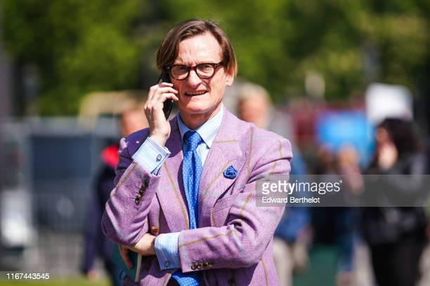 Hamish Bowles wears a blue thin stripes white shirt a blue tie with white polka dots a light purple jacket with yellow stripes bejewelled cufflinks...