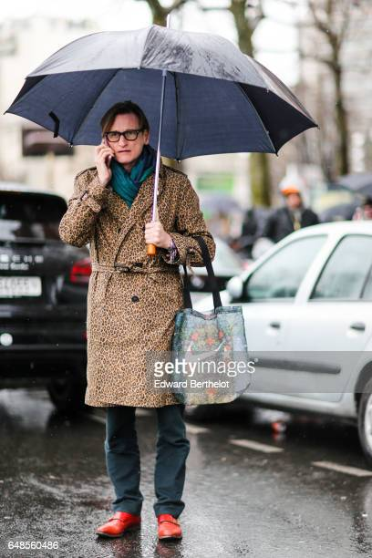 Hamish Bowles wears a scarf a leopard print trenc coat green pants and red leather shoes and an umbrella outside the Celine show during Paris Fashion...