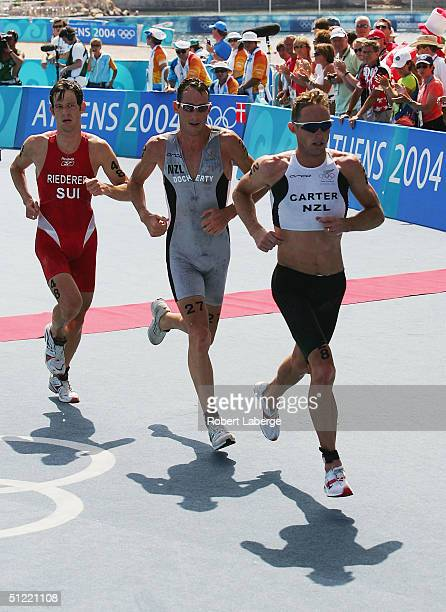Hamish Carter and Bevan Docherty of New Zealand lead Sven Riederer of Switzerland during the run leg in the men's triathlon on August 26 2004 during...