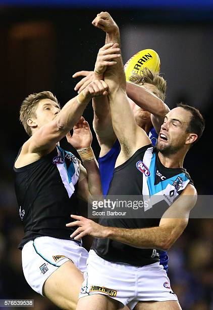 Hamish Hartlett and Matthew Broadbent of the Power compete for the ball with Jack Ziebell of the Kangaroos during the round 17 AFL match between the...