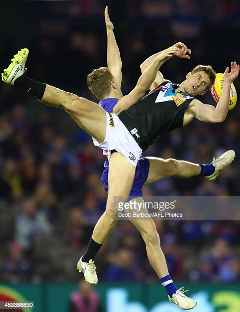 Hamish Hartlett of Port Adelaide and Lachie Hunter of the Western Bulldogs compete for the ball during the round 19 AFL match between the Western...