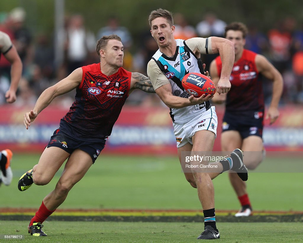Hamish Hartlett of Port Adelaide is chased by Dean Kent of the Demons during the round 10 AFL match between the Melbourne Demons and the Port Adelaide Power at Traeger Park on May 28, 2016 in Alice Springs, Australia.