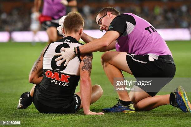 Hamish Hartlett of Port Adelaide is helped by a trainer after a heavy hit from Patrick Dangerfield of the Cats during the round five AFL match...