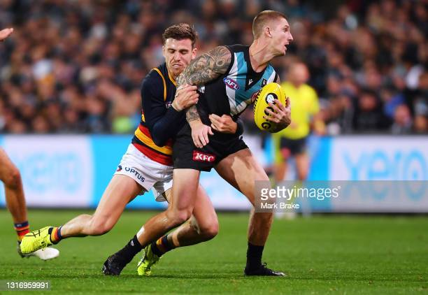 Hamish Hartlett of Port Adelaide tackled by Paul Seedsman of the Crows during the round eight AFL match between the Port Adelaide Power and the...