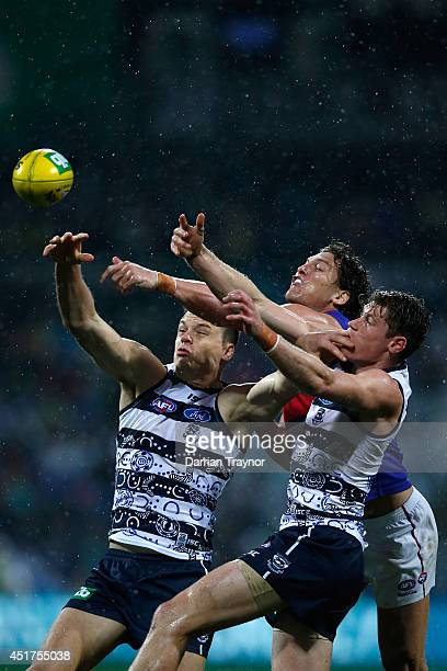 Hamish McIntosh and Mark Blicavs of the Cats compete against Will Minson of the Bulldogs during the round 16 AFL match between the Geelong Cats and...