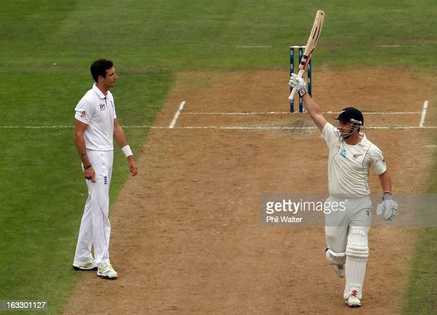 Hamish Rutherford of New Zealand celebrates his century as Steven Finn of England looks on on day three of the First Test match between New Zealand...