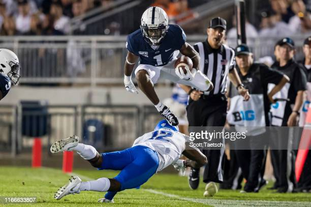 Hamler of the Penn State Nittany Lions hurdles Devon Russell of the Buffalo Bulls during the first half at Beaver Stadium on September 07 2019 in...