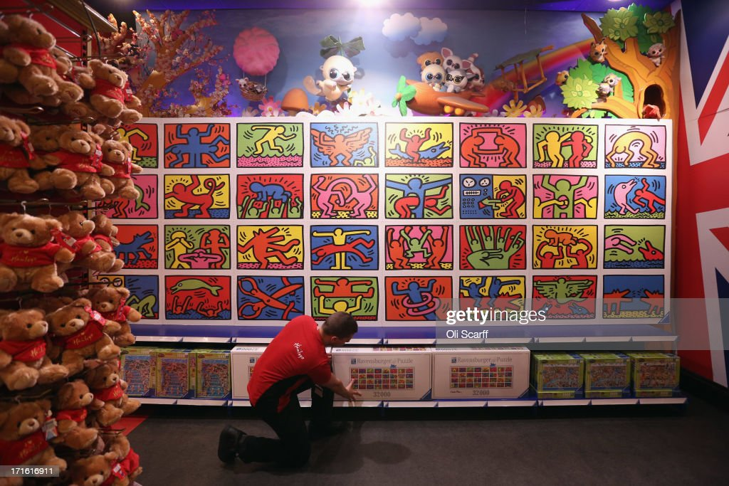 A Hamleys employee adjusts a box for the 32,256-piece Keith Haring jigsaw, beneath the completed puzzle, in Hamleys toy shop on June 27, 2013 in London, England. The jigsaw, which retails for 200 GBP and is the largest commercially available jigsaw in the world, is included in Hamleys' predictions for the top selling toys for Christmas 2013.