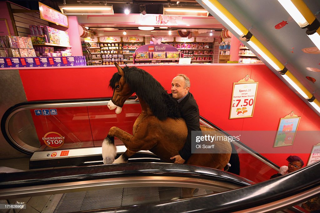 A Hamleys employee carries a Clydesdale Prancing Pony through the toy shop on June 27, 2013 in London, England. The soft toy pony retails for 850 GBP and is included in Hamleys' predictions for the top selling toys for Christmas 2013.