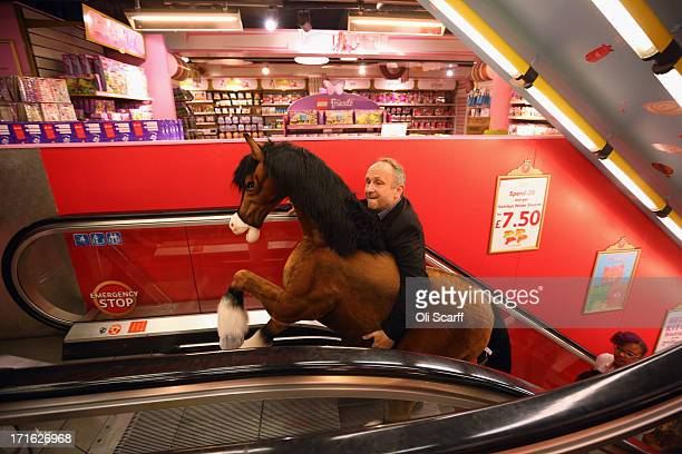 Hamleys employee carries a Clydesdale Prancing Pony through the toy shop on June 27 2013 in London England The soft toy pony retails for 850 GBP and...