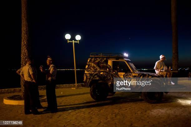 Hammamet, Tunisia, 11 August 2016. A graffiti artist sits on a tagged car while police patrol.