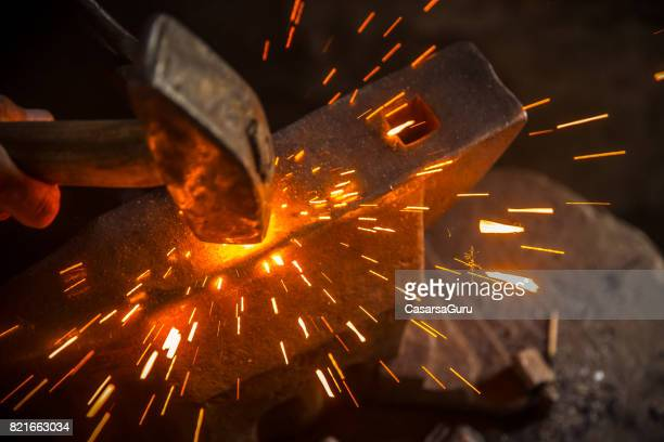 a hammer beat causes sparks - blacksmith shop stock photos and pictures