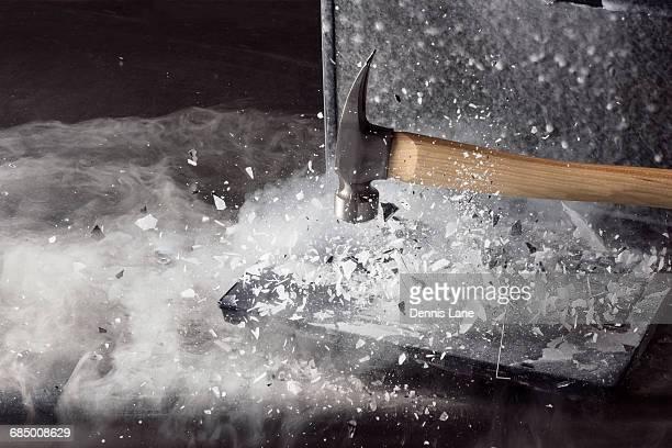Hammer breaking ice on frozen laptop