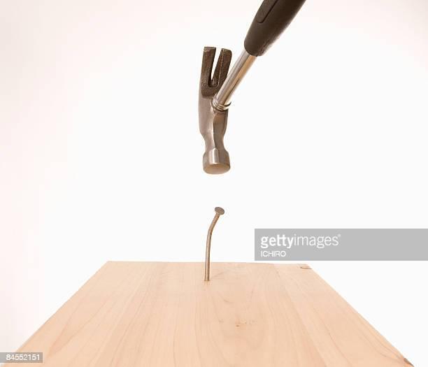 Hammer drives a nail into the wood