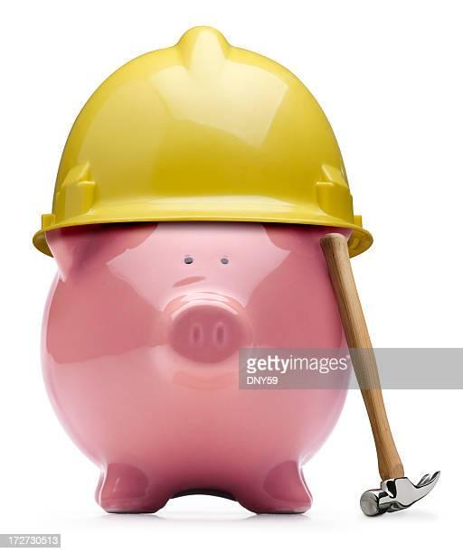 Hammer gelehnt gegen Rosa Sparschwein mit Schutzhelm