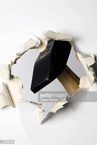A hammer making hole in a wall