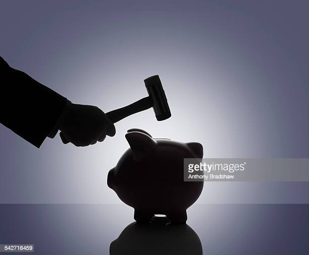 Hammer poised over a piggy bank
