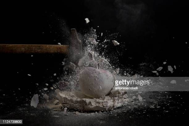 hammer smashing a mould of a chalk apple into pieces - hammer stock pictures, royalty-free photos & images