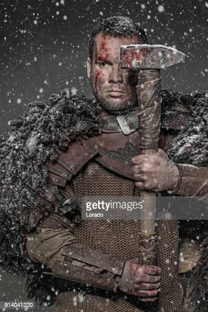 Hammer wielding viking warrior brunette male in wild highland countryside