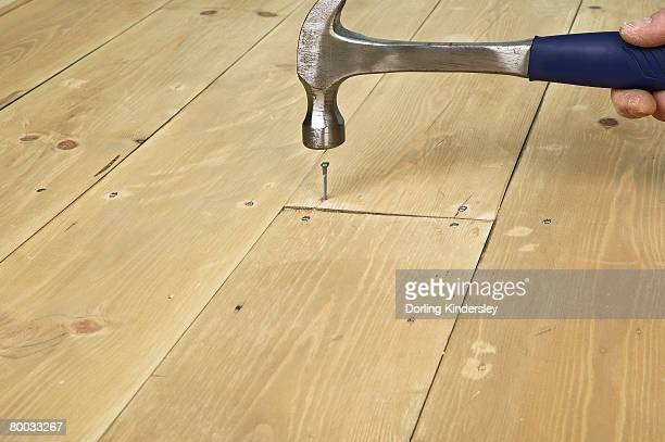 hammering a nail in to a floor board - floorboard stock photos and pictures