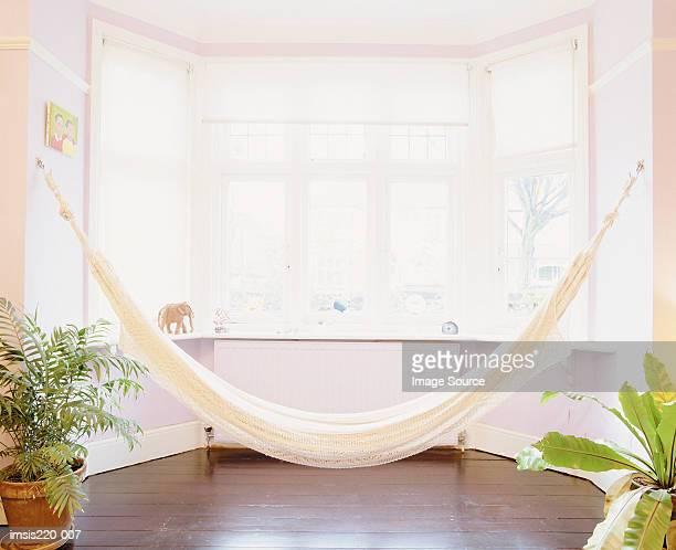 A hammock by a bay window
