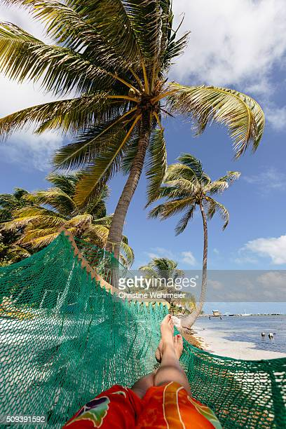 Hammock time. Personal point of View. Lady in an orange sarong lying in a green hammock underneath a blue sky and palmtrees