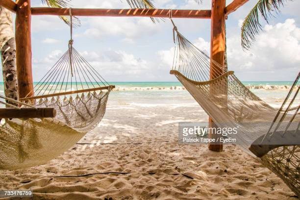 Hammocks Hanging On Beach Against Cloudy Sky